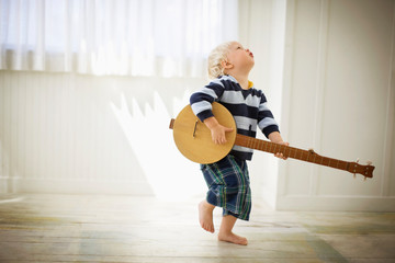 Toddler playing with a wooden banjo.