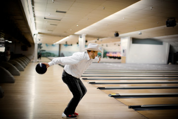 Mid-adult bearded man wearing a cowboy hat holding a bowling ball and preparing to through it inside a bowling alley.