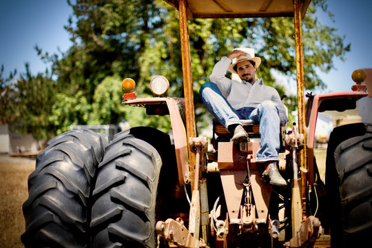 Portrait of a mid-adult man adjusting his hat while sitting on top of a tractor in a field outdoors in the sunshine.