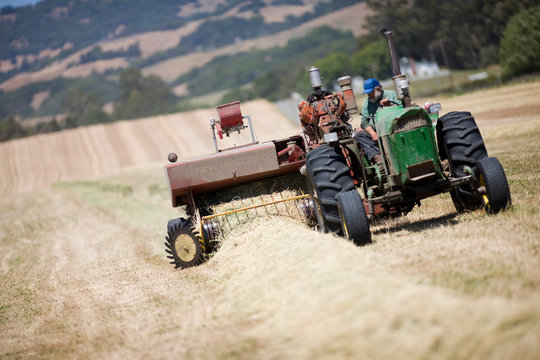 Tractor creating hay bales in field