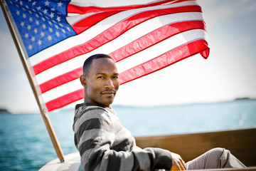 Man on boat sitting under the American flag