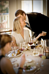 Man whispering to a woman at a dinner party