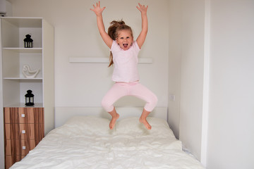 Little girl jumping on bed at home