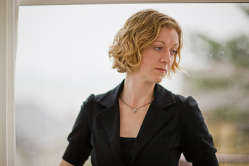 Portrait of serious woman standing next to window
