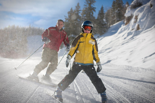 Happy father and young son skiing on a mountain slope.