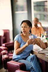 Happy mid adult woman enjoying a milkshake at a diner.
