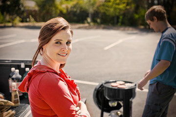 Portrait of a smiling young woman standing next to her boyfriend who is cooking on a barbeque grill.