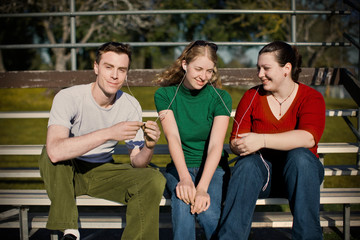 Three teenagers sharing headphones to listen to music on an MP3 player while sitting in bleachers outdoors in the sun.