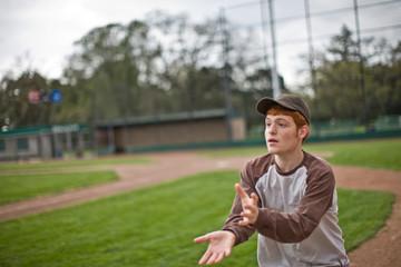 Boy catching ball on baseball pitch