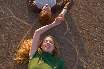 Portrait of a smiling teenage couple holding hands lying on their backs on a heart shape drawn in the dirt.