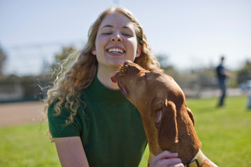Smiling teenage girl being licked on the chin by her brown dog while at the park.
