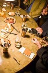 Group of people drinking wine around a table of appetizers.
