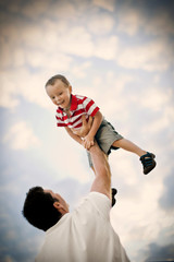 Smiling young boy being held aloft by his father.