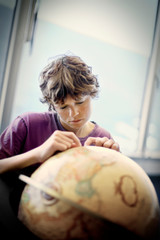 Teenage boy looking at a globe of the world.