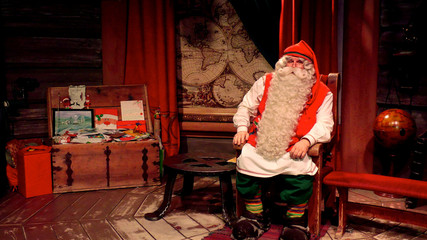 A man dressed as Santa Claus poses for a picture at the Santa Claus Office located on the Arctic Circle near Rovaniemi