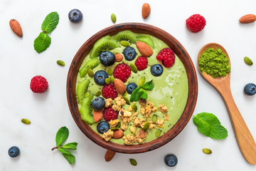 matcha green tea smoothie bowl with fresh fruits, berries, nuts, seeds and granola with a spoon for healthy breakfast