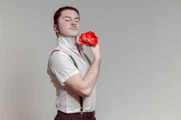 Adult Italian man with mustache posing with flower in hand. He seems to be sad with broken heart or something…?