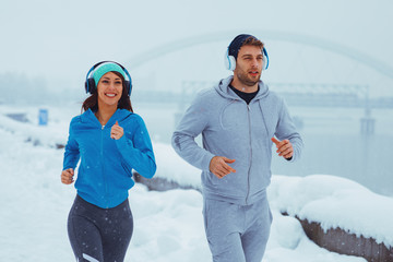 Young couple running on a snowy day