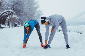 Young sports couple stretching on snowy day in the city