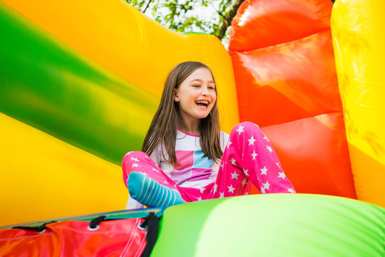 Happy little girl having lots of fun on a jumping castle during sliding.