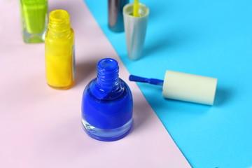 Blue and green nail lacquer bottles and nail brushes on blue and pink background