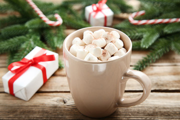 Cappuccino with marshmallows in cup and gift box on wooden table