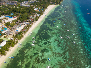 Aerial drone view of Alona beach at Panglao island. Beautiful tropical island landscape with traditional boats, sand beach and palm trees. Bohol, Philippines.