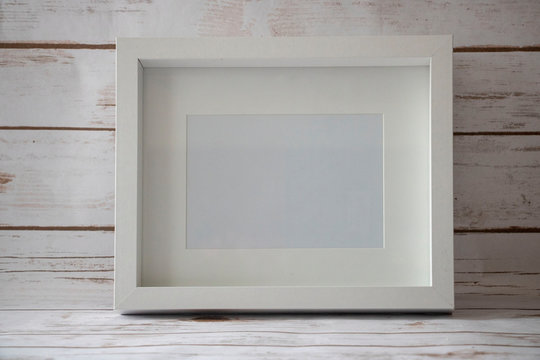 A horizontal 5x7 white frame and a white wooden background.