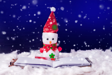 Toy snowman in front of an open book. Fiction reading. Snowman on a dark background during the snowfall. Happy Christmas and New Year's greetings_