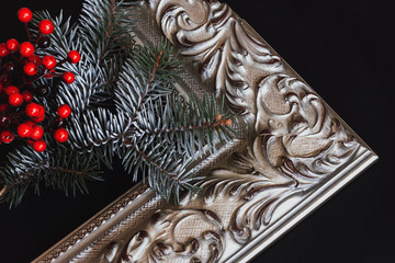 Picture frame with pine branch and holly on black background.