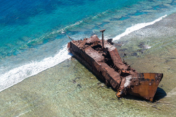 """Aerial view of the shipwreck site of 1965 of Motor vessel """"Ever Prosperity"""" cargo ship from Monrovia, Liberia. West Coast barrier reef, Coral sea, New Caledonia, South Pacific Ocean."""