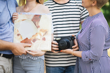 Family in the hands of an album with photos and a camera