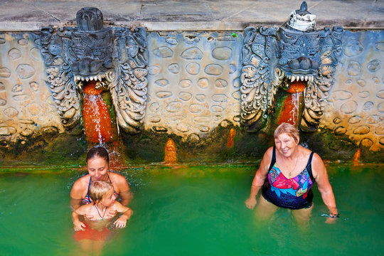 People stand in thermal bath, relaxing under flowing water stream of fountain in natural hot spring Air Panas Banjar. Activity at family day tour on summer vacation. Popular travel destination in Bali
