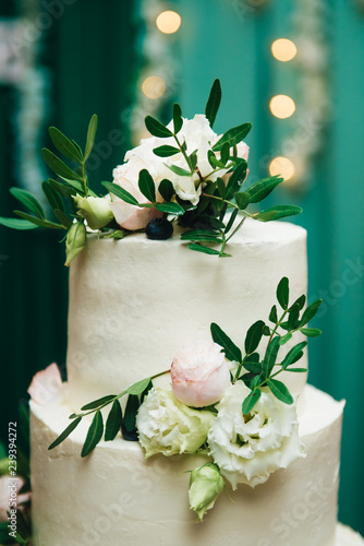 Three Tiered Wedding Cake With Fresh Flowers On A Green Background