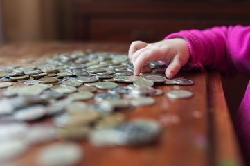 The children hand counts Russian coins scattered on the table