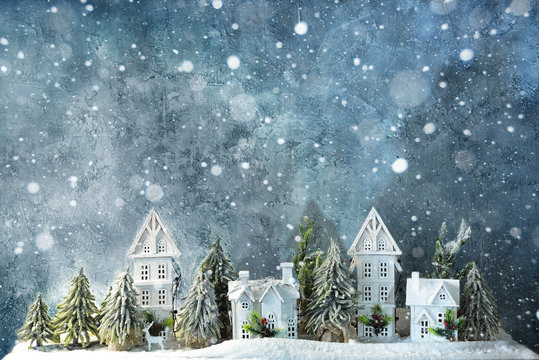 Frosty winter wonderland forest with snowfall, houses and trees. Christmas greetings concept