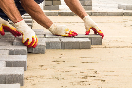workers lay paving tiles, construction of brick pavement, close up architecture background