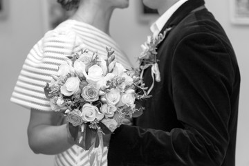 Bride and groom are holding a bouquet of roses, close-up, black and white photo