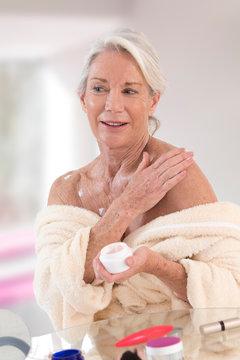 Lovely senior Woman applying moisturizer cream on her body