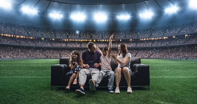 A family is watching a soccer moment, sitting on the couch located in the middle of the soccer stadium.