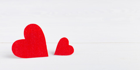 Red hearts of different sizes on a white background. Harvesting cards for Valentine's Day. Place for text, copy space.