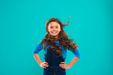 Little girl with long hair. Kid happy cute face with adorable curly hair stand over blue background. Pure beauty. Beauty tips for tidy hair. Kid girl long healthy shiny hair wear casual clothes