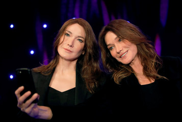 Singer Carla Bruni-Sarkozy poses with her wax figure made by German sculptor Claus Velte at the Grevin wax museum during the presentation of her waxwork in Paris