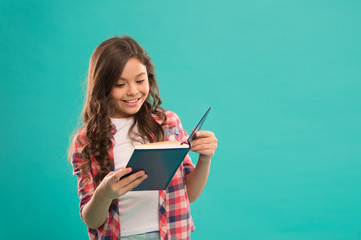 Towards knowledge. Girl hold book read story over blue background. Child enjoy study and reading book. Book store concept. Wonderful free childrens books available to read. Childrens literature