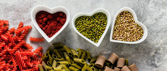 banner of multicolor gluten-free pasta with ingredients in bowls in the form of hearts from which it is made on a stone table