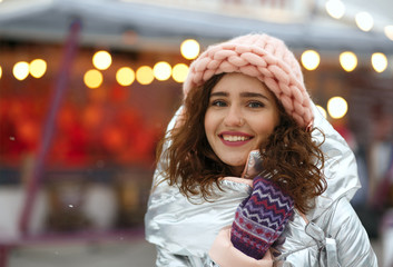 Winter portrait of positive brunette young lady wearing warm trendy outfit, walking at the Christmas fair in Kyiv. Space for text