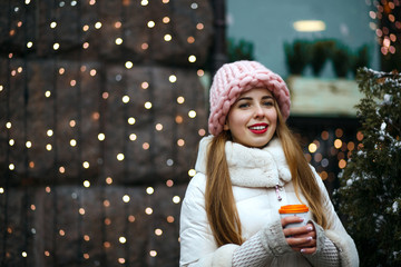 Winter portrait of beautiful brunette young lady wearing warm trendy outfit, drinking hot coffee at the street. Space for text