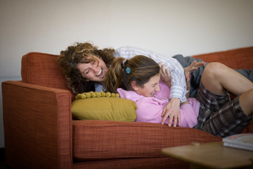 Mid-adult business woman hugging her teenage daughter on a couch.