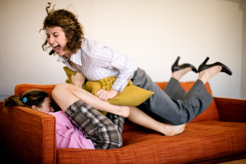 Mid-adult business woman playing with her teenage daughter on a couch.
