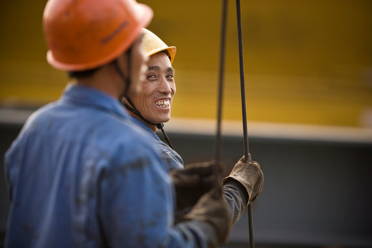 Two mid-adult male construction workers in a construction site.